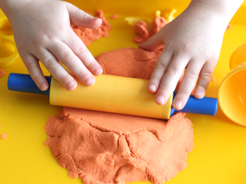 Use rolling pin on kinetic sand