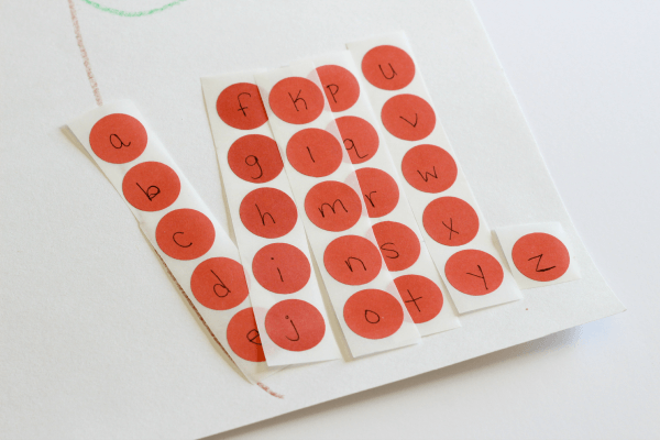Red dot stickers for apples on a tree.