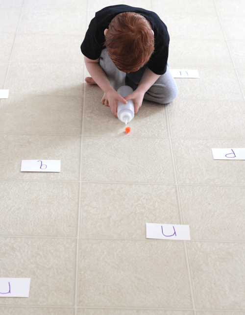 Squeeze bottle blows pom pom toward letters on the ground