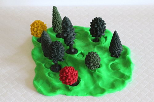 Plant toy trees in play dough