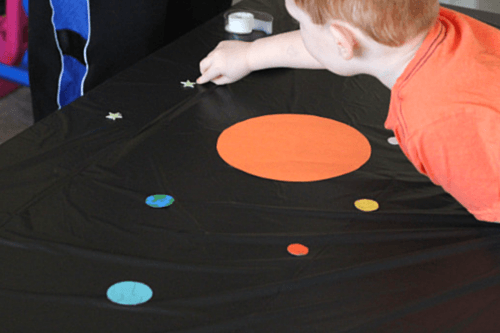 Tape planets and stars to a black tablecloth.