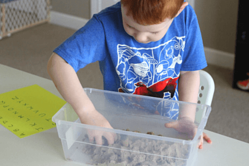Dig into the kinetic sand and search for the tiny letter beads
