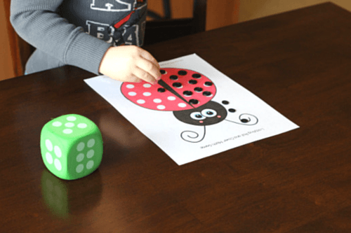 Roll dice and cover spots on ladybug with black buttons