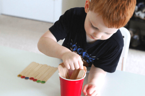 Pull a craft stick out of the cup and identify the letter