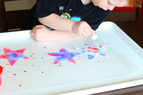 Use droppers to squirt paint onto coffee filter stars.