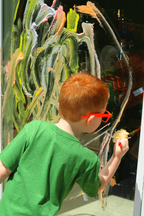 Use paintbrushes or hands to paint on the window.