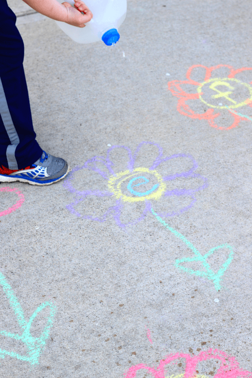 Draw sidewalk chalk flowers on cement.