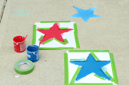 Tape star stencils to driveway and paint inside with red and blue paint.