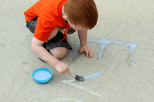 Trace letters with sidewalk chalk paint on the driveway.