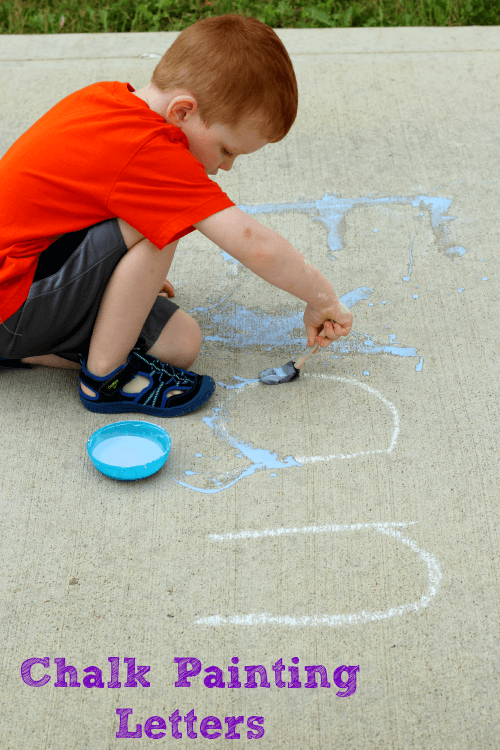 Painting alphabet letters with sidewalk chalk paint.