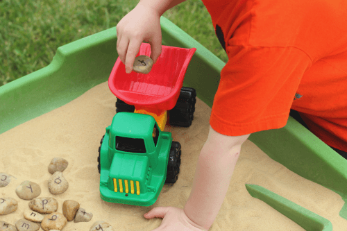 Write letters on rocks and add them to the sandbox. Then do this fun letter learning activity!