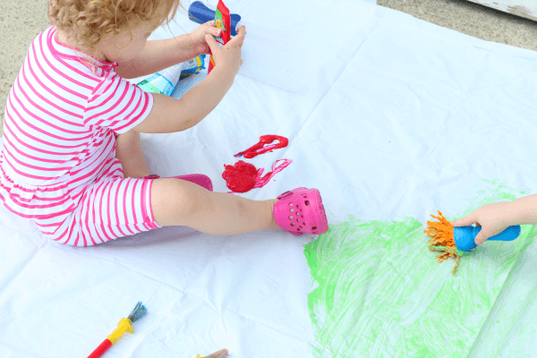 Fine motor practice with an outdoor preschool art activity.