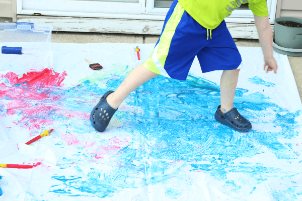Run threw paint and paint with your feet.
