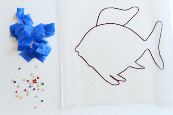 Decorating a rainbow fish with tissue paper and sequins.