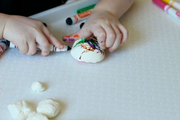 Decorating clay eggs with markers to makers. A fun dinosaur craft!