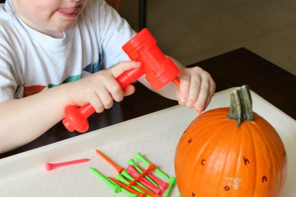 Pounding pumpkins with a hammer. Gross motor pumpkin activity.