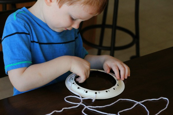 Lacing a spider web fine motor activity for learning letters.