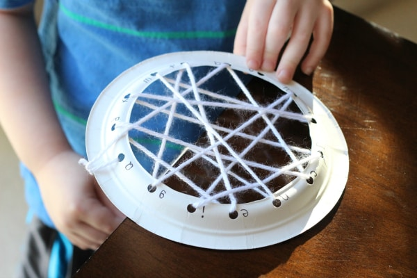 Spider web weaving activity for fine motor skills and teaching the alphabet.