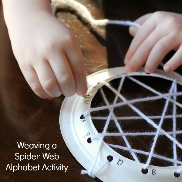 Weaving a spider web alphabet activity for preschoolers.