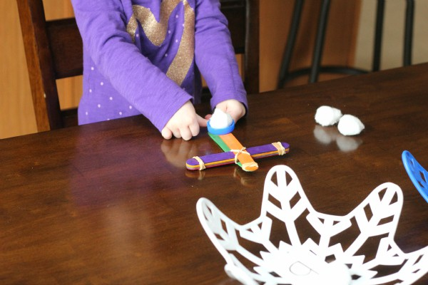 Toddler STEM activity for winter. A fun snowball catapult activity that toddlers will love!