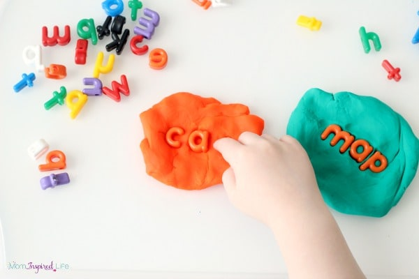 Stamping the alphabet in play dough. A hands-on way to learn the alphabet.