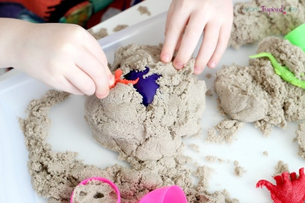 Kinetic sand dinosaur activity that uses Easter eggs. A fun sensory tray for kids!