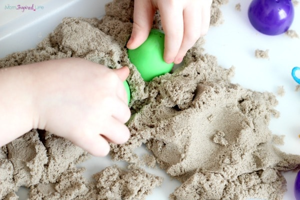 Using Easter eggs as kinetic sand molds. A fun sensory activity!