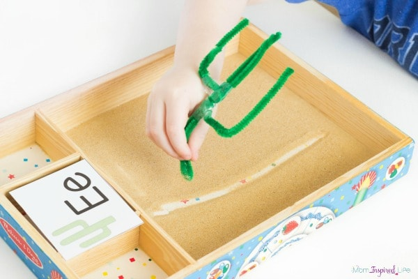 Learning to write with a sand tray and alphabet cards.
