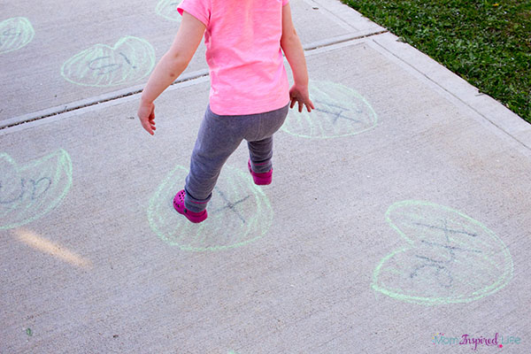 Frog hop game for toddlers. This is a great way for them to develop gross motor skills and learn things like letters, shapes and numbers.