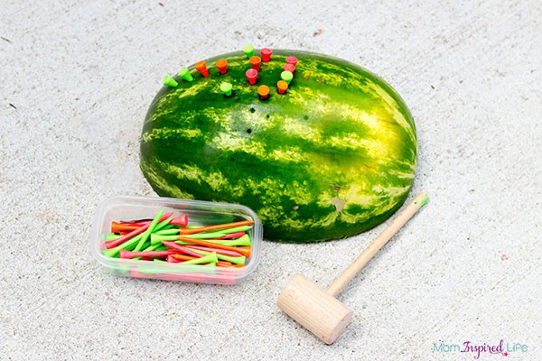 Hammering tees into watermelons is a super fun way to develop fine motor skills!
