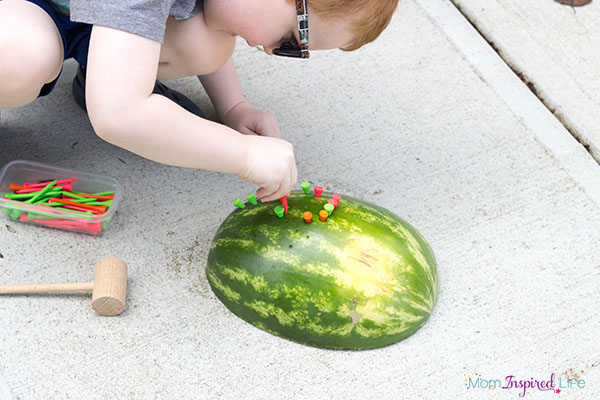 Pushing golf tees into watermelons for fine motor skills development.