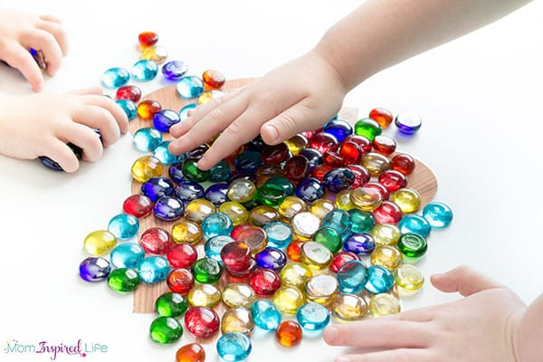 Letter tracing with loose parts. A hands-on literacy activity for preschoolers.