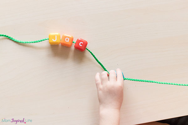 Alphabet lacing beads to develop fine motor skills in preschoolers.