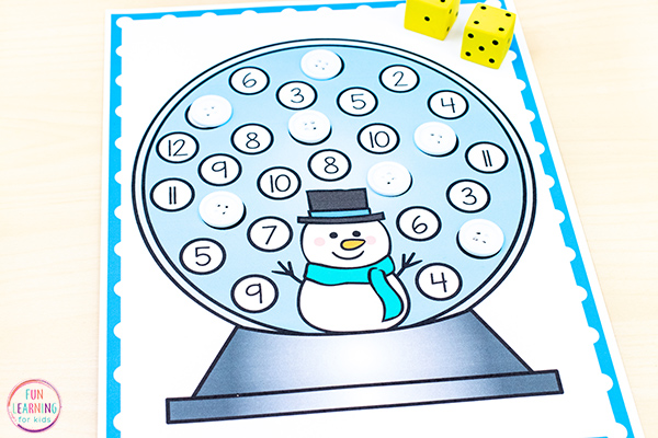 Snow globe mats with numbers 2-12 on it in white dots. Students roll the two dice and cover the right space with a white button.
