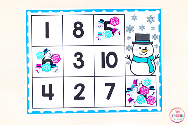 Free printable snowman theme counting mats with a snowman and snowflakes on it.